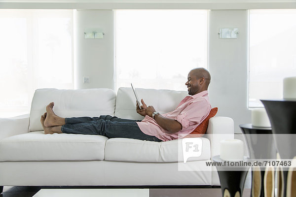 Black man on sofa using digital tablet