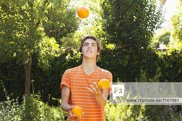 Caucasian teenager juggling oranges