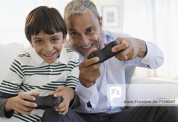 Hispanic grandfather and grandson playing video game