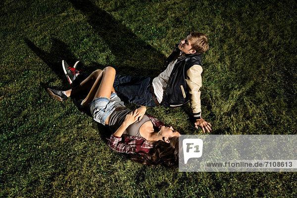 Couple lying on grass at night  high angle