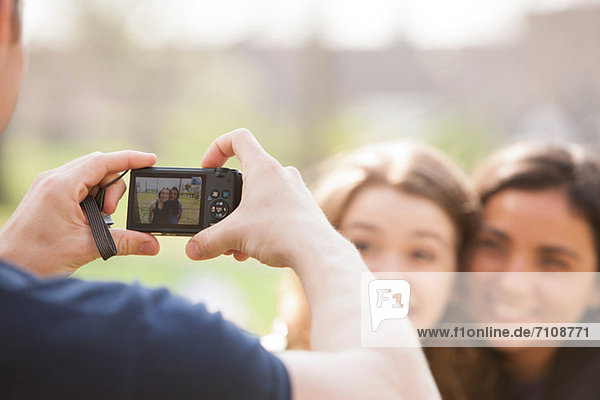 Man taking a photograph of two young women