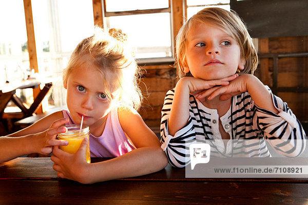 Mädchen trinkt Saft und Junge sieht nachdenklich aus.