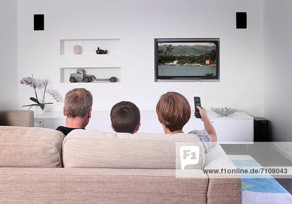 Familie auf dem Sofa beim Fernsehen  Rückansicht