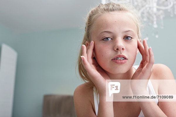 Teenagermädchen berührt ihr Gesicht