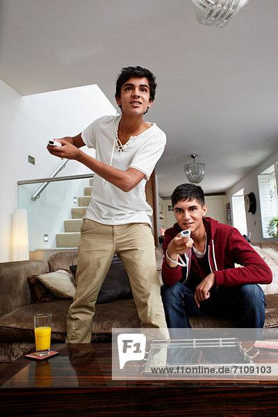 Teenage boys playing video game