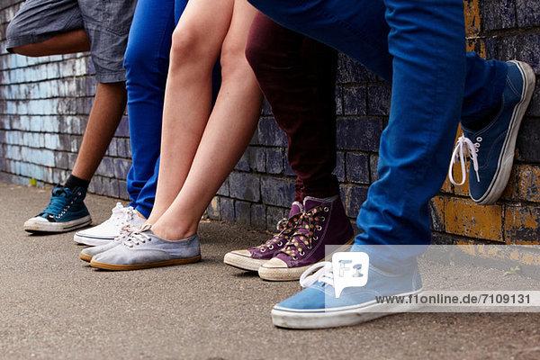 Beine von Teenagern  die in einer Reihe stehen