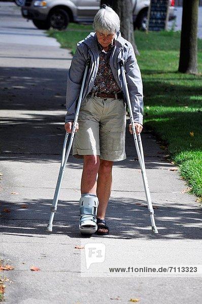 Außenaufnahme  Frau  gehen  offen  Stiefel  Verletzung  Langsamkeit  Unterarmgehstütze  Kanada  Ontario  freie Natur  rechts