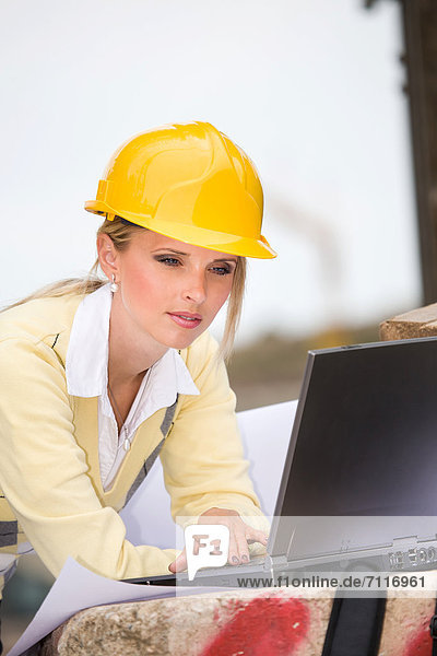 Junge weibliche Bauunternehmerin auf einer Baustelle