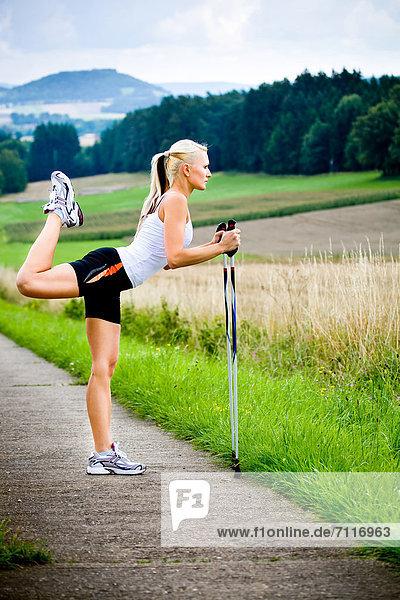 Junge Frau beim Stretching  Nordic Walking