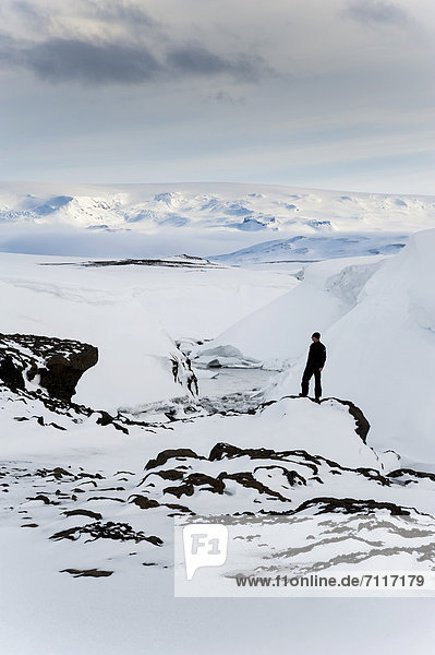 Man standing on a frozen and snow-covered river  winter landscape  Vatnajoekull Glacier  Icelandic Highlands  Iceland  Europe
