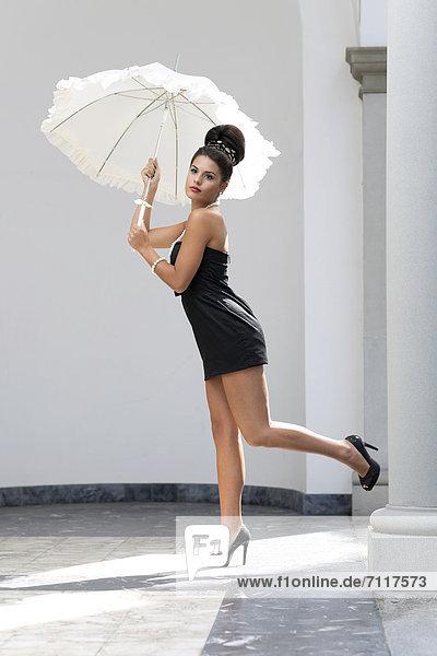 Junge Frau mit Hochsteckfrisur  weißem Schirm  schwarzem kurzen Kleid und hohen Schuhen  Fashion
