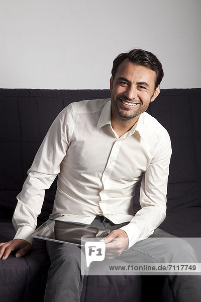 Lächelnder Mann mit iPad auf Sofa