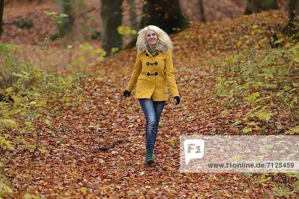 Fröhliche blonde junge Frau im Wald