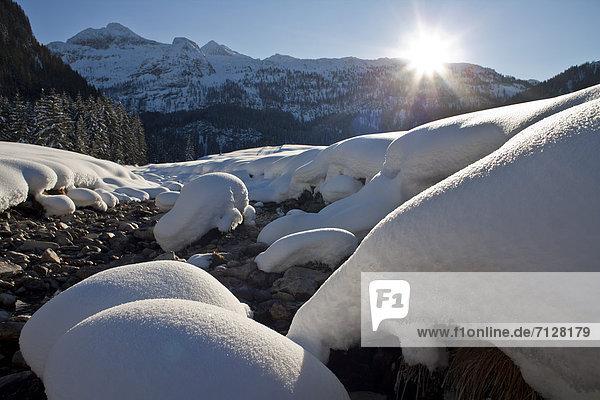 Landschaftlich schön  landschaftlich reizvoll  Winter  Schnee  Bach  Gegenlicht  Österreich  Salzburg  Sonne