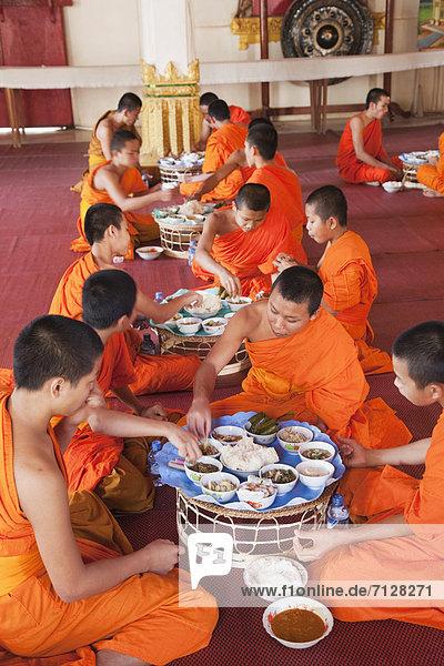 Vientiane  Hauptstadt  Urlaub  Lebensmittel  Reise  Asiatische Küche  Buddhistischer Tempel  fünfstöckig  Buddhismus  essen  essend  isst  Mönch  Asien  Laos  Tourismus
