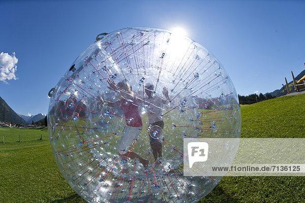 durchsichtig  transparent  transparente  transparentes  Jugendlicher  Europa  Frau  Mann  Wiese  Ball Spielzeug  Österreich  Spaß
