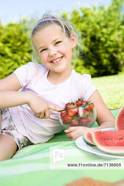 Mädchen isst Erdbeeren im Garten
