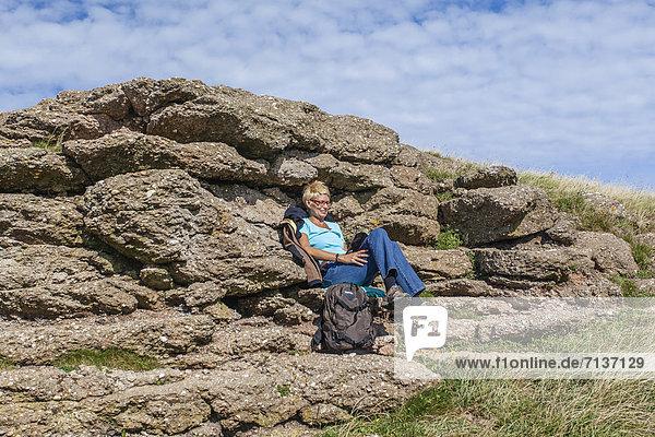 Frau sitzt vor einem Felsen und liest ein Buch  Insel Helgoland  Schleswig-Holstein  Deutschland  Europa