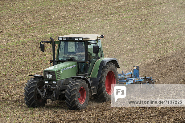 Traktor mit Grubber auf Acker  Deutschland  Europa  öffentlicherGrund