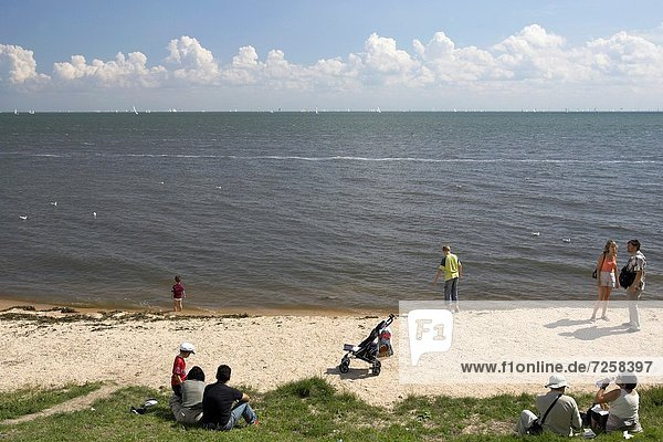 Visitors enjoy the small beach at Volendam fishing village The Netherlands
