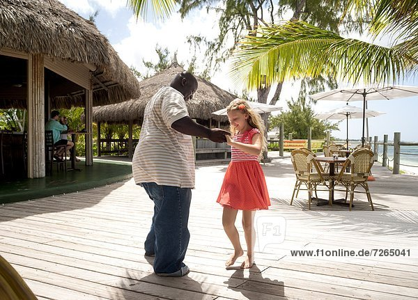 Local man dancing with a smiling preteen girl in Providenciales  Caicos  Turks and Caicos Islands  West Indies  Caribbean  Central America