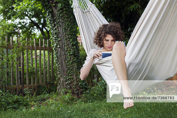 young woman lying in hammock in garden reading