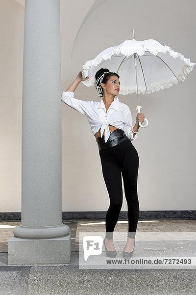 Junge Frau mit Hochsteckfrisur  weißem Hemd  schwarzen Leggins  hohen Schuhen und weißem Schirm