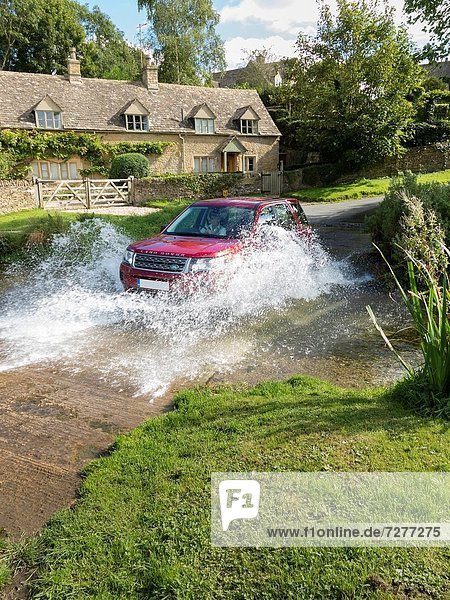 Land rover Freelander crossing a stream  Cotswolds  England