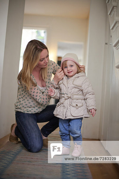 Mutter legt Strickmütze auf die Tochter