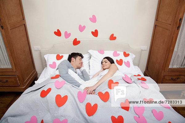 Paar im Bett mit Herzformen auf Bettwäsche