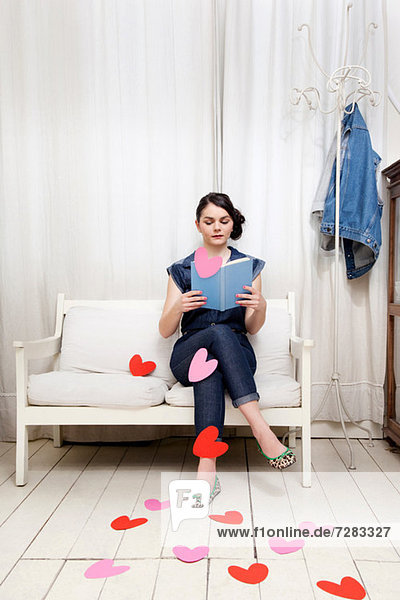 Young woman reading book with heart shapes