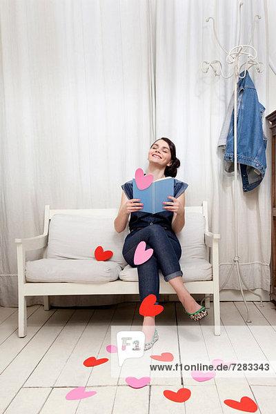 Frau liest Buch mit Herzformen
