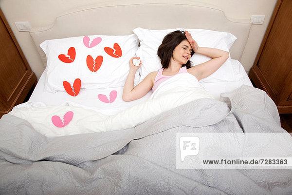 Frau weint im Bett mit gebrochenen Herzformen auf der Bettwäsche