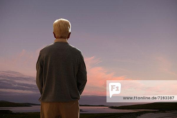 Rückansicht eines älteren Mannes  der bei Sonnenuntergang auf das Meer blickt.