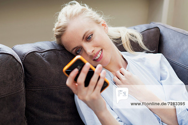 Young woman looking at smartphone and smiling