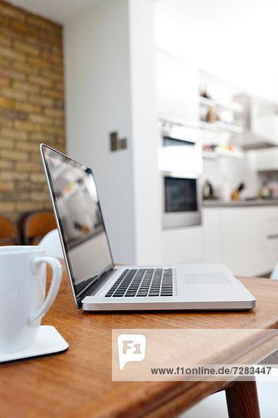 Laptop und Becher auf dem Tisch