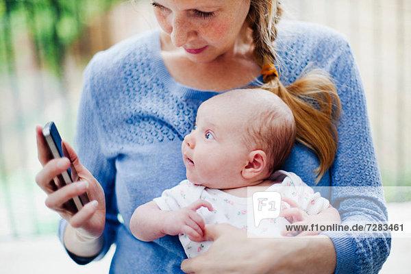 Mutter mit neugeborener Tochter und Handy