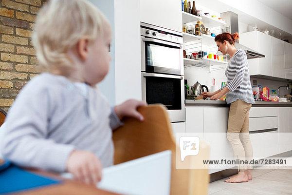 Mutter bereitet das Essen des Sohnes zu.