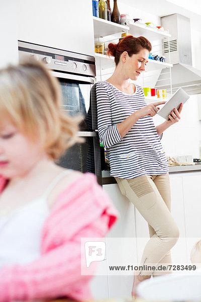 Mutter mit digitalem Tablett  Tochter im Vordergrund