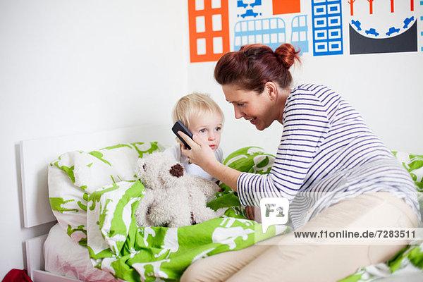 Mutter hält Handy an Söhne Ohr im Bett