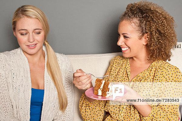 Frau starrt einen Freund an  der Kuchen isst.