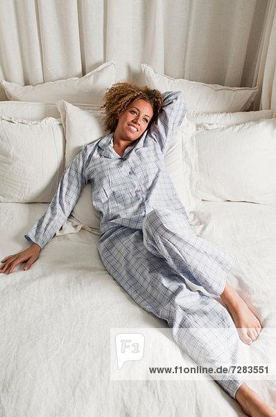 Frau im Schlafanzug im Bett liegend
