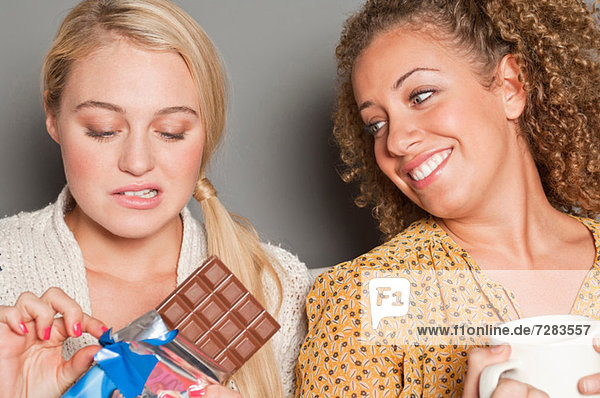 Woman staring at friend holding chocolate mouth