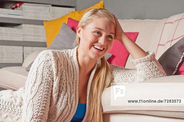Porträt einer Frau  die sich auf dem Sofa stützt.