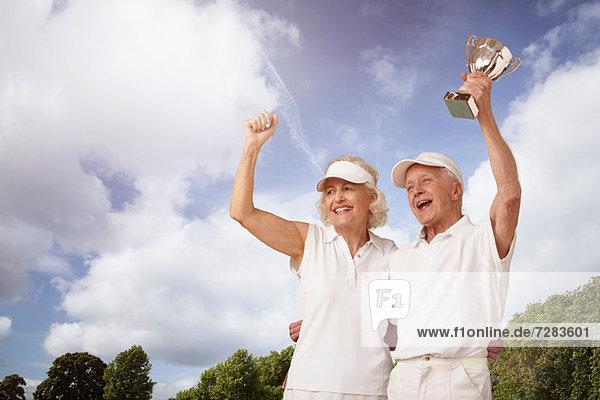 Seniorenpaar hält Tennistrophäe und Jubel