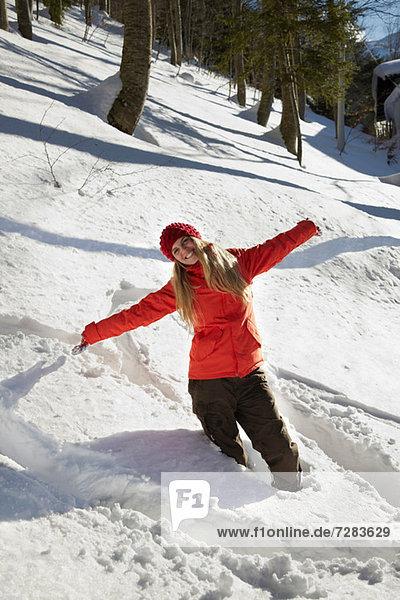 Porträt einer Frau mit rotem Mantel im Schnee  Arme ausgestreckt