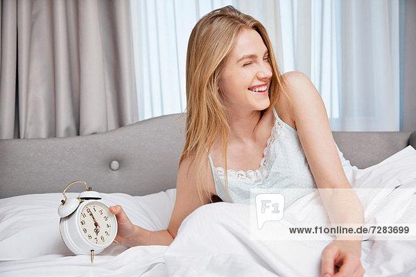Junge Frau im Bett  einen Wecker haltend