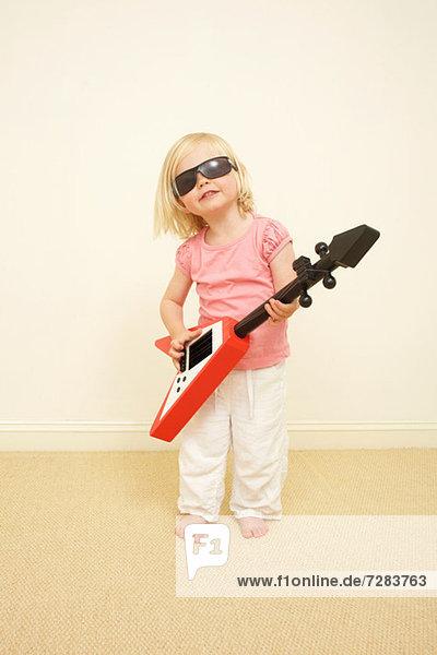 Kleinkind mit Sonnenbrille  spielt Gitarre