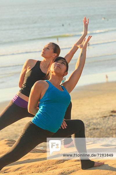Zwei Frauen beim Yoga am Strand