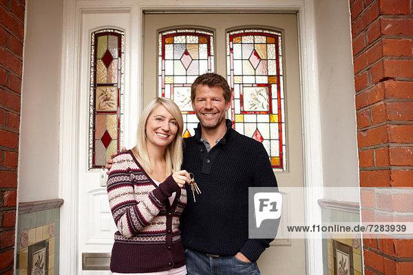Paar außerhalb des neuen Hauses mit Hausschlüssel